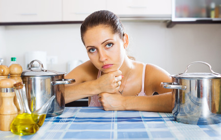 leaning on elbows: Sad young woman leaning her elbows at the kitchen