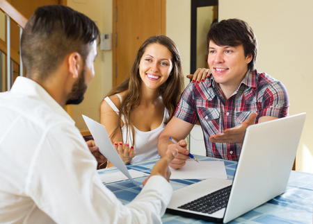 salesman: Smiling young couple and salesman talking cheerfully about purchase Stock Photo