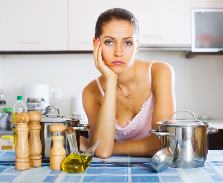in low spirits: Pensive young housewife leaning her elbows at the kitchen