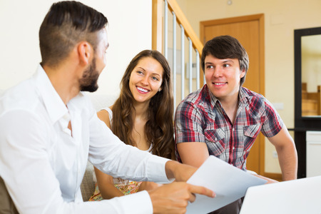 salesman: Couple and salesman talking cheerfully about purchase at home