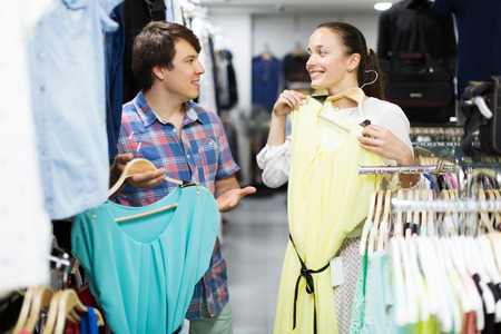 choosing clothes: Merry couple choosing clothes in the shop