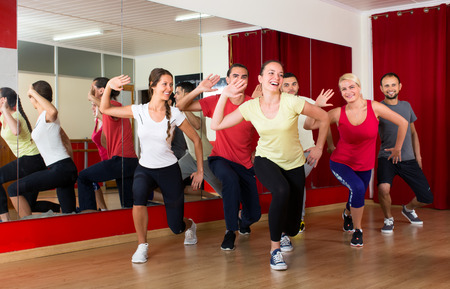 aerobics class: Happy caucasian people dancing in a sports hall on a choreography lesson