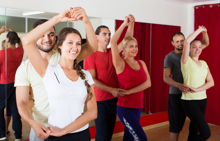 ballroom dancing: Group of adult american people dancing salsa in studio Stock Photo