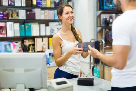 Giovane commesso di un negozio di sesso femminile che serve acquirente alla cassa