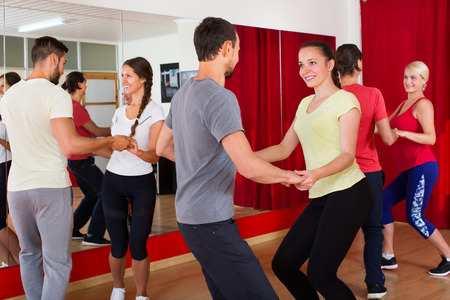 Happy men and women enjoying active dance at a dance studio Stock Photo