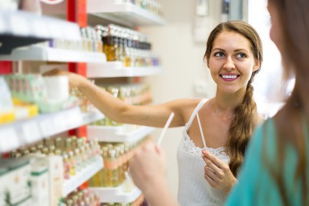 vend: young american girl chooses perfume in the shop