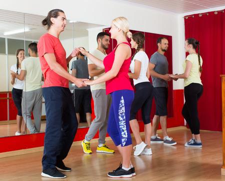 unprofessional: Group of adult european people dancing salsa in studio