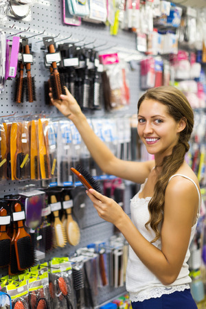 hairbrush: Young smiling woman chooses hairbrush in hardware store Stock Photo