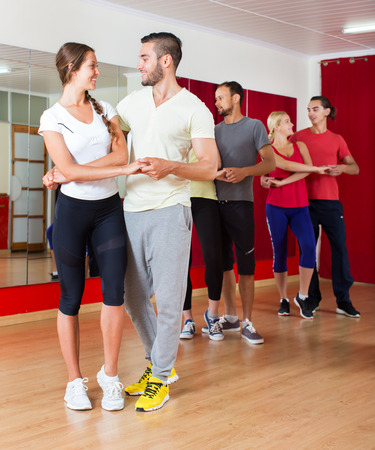 Smiling happy adults dancing bachata together in dance studio