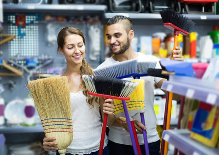 house cleaning: Young happy european  housewife chooses broom for cleaning Stock Photo