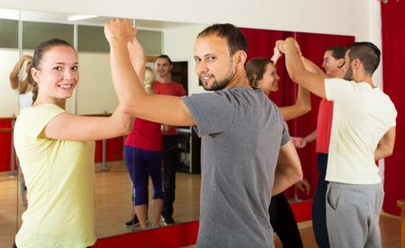 Cheerful young people dancing Latino dance in class