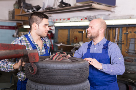 russian car: adult russian car mechanics in coveralls working at carshop Stock Photo