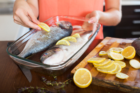 fryingpan: Close-up of woman putting pieces of lemon in fish at  kitchen