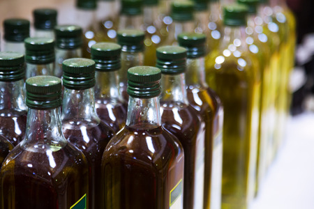 olive oil bottle: Bottles of olive oil on counter in shop Stock Photo