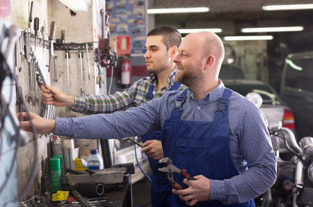 toiling: Portrait of two adult garage colleagues near facilities Stock Photo