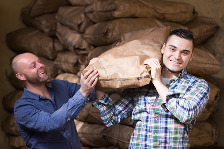 loaders: Two smiling loaders handling sacks with something heavy indoors Stock Photo