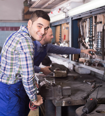 toiling: Two positive workmen toiling in the locksmiths workshop and smiling Stock Photo
