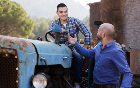 sucessful: Two farmers talking near the agricultural machinery in the shed Stock Photo