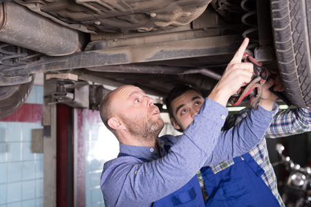 hard work: Two man fixing car tire leak Stock Photo