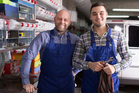 toiling: Portrait of two happy garage colleagues near facilities