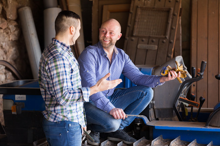 workplace wellness: Two farmers talking near agricultural machinery at the shed