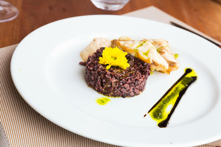 black rice: Codfish with black rice and sauce on white plate Stock Photo