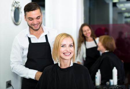salon de belleza: Retrato de la hermosa mujer sentada en un salón de belleza en un salto de cama negro mientras peluquería está preparando para lavarse el pelo