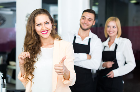hairtician: Happy woman standing in a hair salon touching her hair and showing thumbs up sign while hairdressers are standing in the back Stock Photo