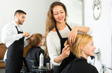 hairdressing: Smiling client sitting in a hair salon while hairdresser is combing her hair. Focus on client