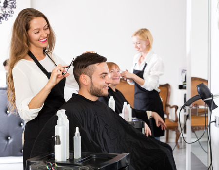 scissors hair: Cheerful young guy cuts hair at the hair salon Stock Photo