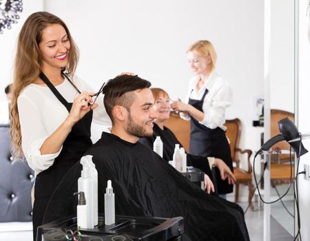 Fröhliche junge Mann schneidet Haare am Haarsalon