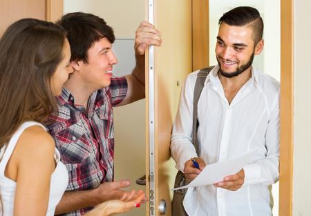 puertas abiertas: sonriendo vendedor europeo presenta su proyecto de pie cerca de la puerta de entrada