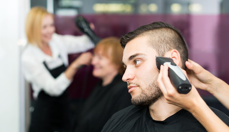 scissors hair: Beautiful man cuts hair at the hair salon Stock Photo