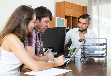 meaningful: Serious bank employee trying hard to make young couple pay back a loan