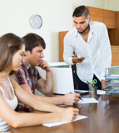 repayment: Agent at the office clamouring credit repayment from young couple