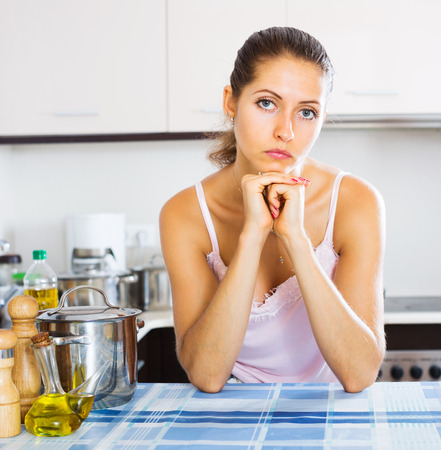 dispirited: Tired young woman leaning her elbows at the kitchen