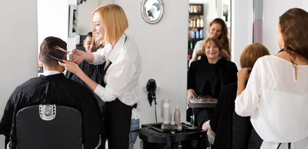 hairtician: Hairdressers cutting hair on their clients indoors in a hair studio