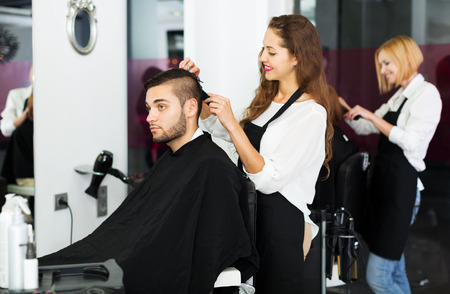 haircutter: Hairstylist makes the cut for man in the barbershop Stock Photo