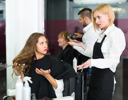 peignoir: Displeased young girl has a serious conversation with the hairdresser Stock Photo