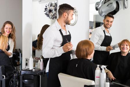 Barber Coupe Les Cheveux Femme D Age Mur Au Salon De Coiffure Banque