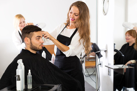 peignoir: guy cuts hair and female barber at the hair salon. Focus on the man Stock Photo