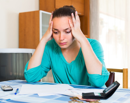 irresponsible: Young woman sitting depressed at the table because of bills