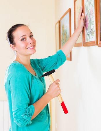 parade of homes: Ordinary young woman with picture and hammer in her hand at house Stock Photo