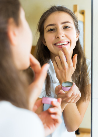 youngster  girl: Happy beauty teenager applying lipstick in front of a mirror at home