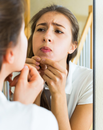 squeezing: Girl squeezing pimple at a home