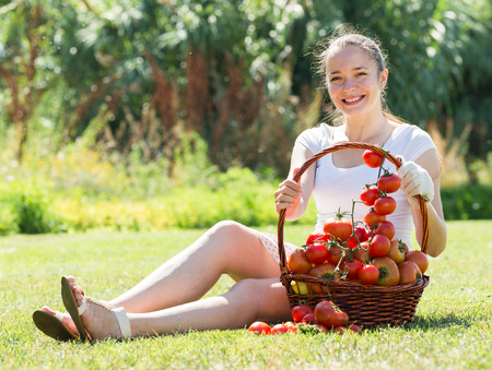 20 years old: Young woman 20 years old with basket of harvested tomato in garden