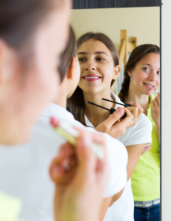 makeups: Young beautiful woman making make-up near mirror. Focus on the left woman Stock Photo