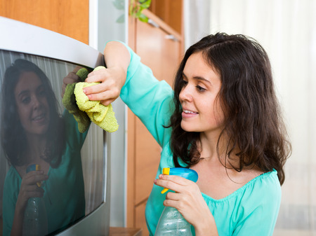 household tasks: Young happy woman wiping the dust on TV in living room at home Stock Photo