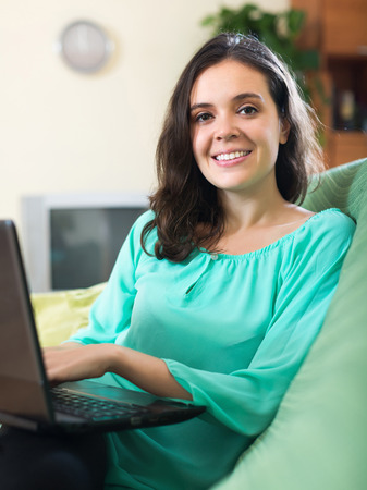 netbook: Young smiling girl looking at netbook in living room Stock Photo
