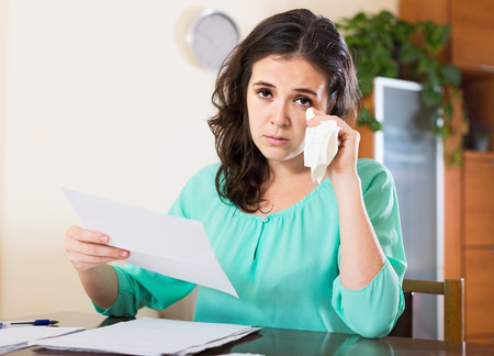 utility payments: Sad woman working with financial documents